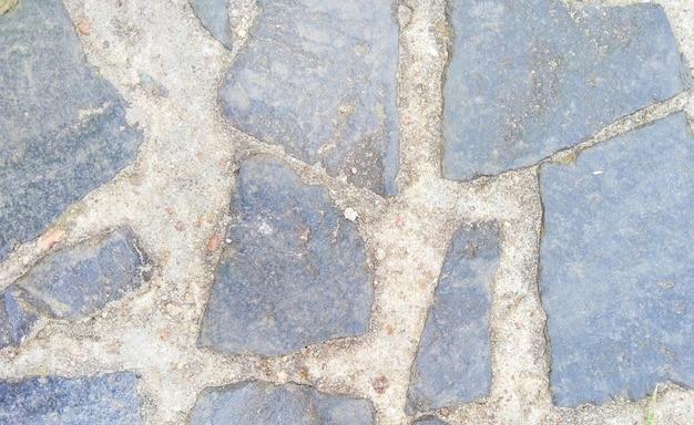 Hintergrund aus dunkelgrauen pflasterplatten in verschiedenen formen und sand