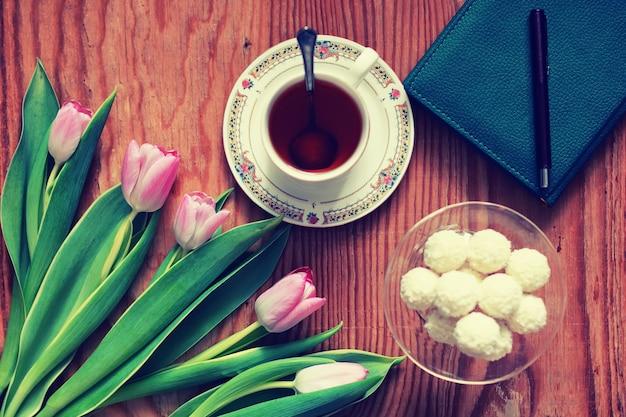Hintergrund aus holz mit tulpe und tee