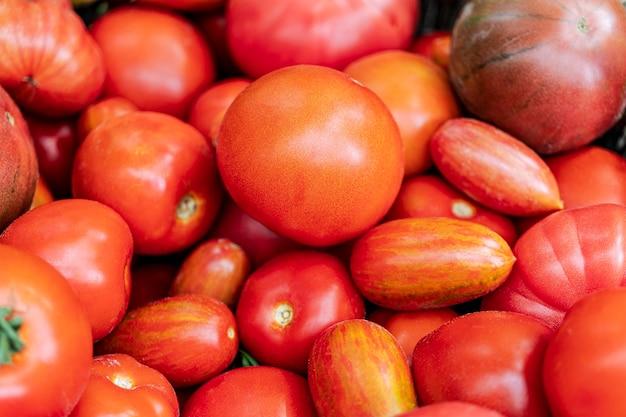 Hintergrund aus natürlichen frischen roten tomaten ohne zusätzliche verarbeitung. das konzept der nicht-gvo-naturprodukte.