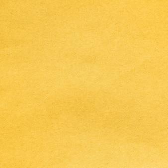 Hintergrund aus recyceltem karton, der in der trendfarbe fortuna gold des jahres 2021 gefärbt ist. nahaufnahme detailansicht abstrakte textur recyceltes umweltfreundliches kartonmaterialmuster, hintergrund für design
