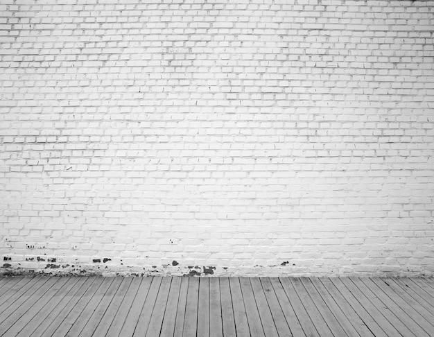 Hintergrund aus weißer backsteinmauer und holzboden