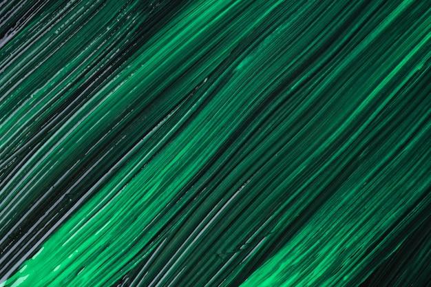 Hintergrund der abstrakten kunst dunkelgrüne und schwarze farben. aquarellmalerei auf leinwand mit smaragdgrünen strichen und spritzern. acrylbild auf papier mit pinselstrichmuster. textur-hintergrund.