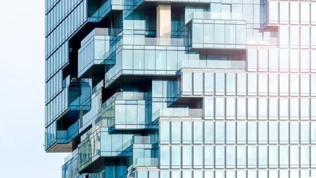 Hintergrund der blauen glasverglasung der modernen gebäudearchitekturwand im musterwürfel und in der quadratischen überschneidung mit beleuchtungssonnenlicht