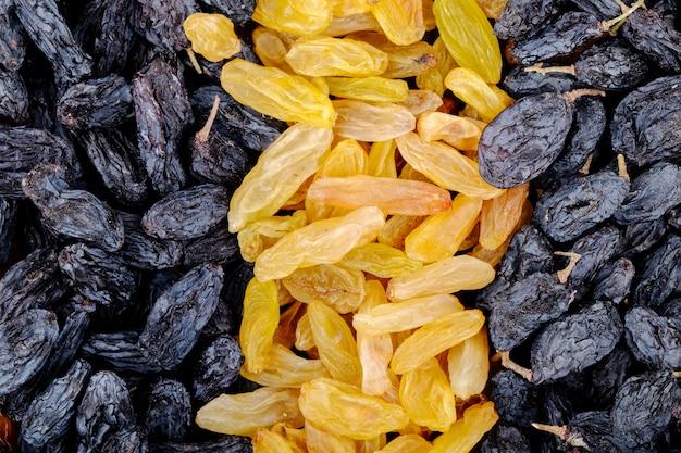 Hintergrund der draufsicht der schwarzen und gelben rosinen der getrockneten früchte