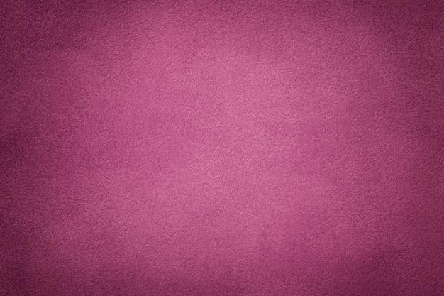 Hintergrund der dunkelpurpurnen veloursledergewebenahaufnahme. samtmatte textur aus wein-nubukleder