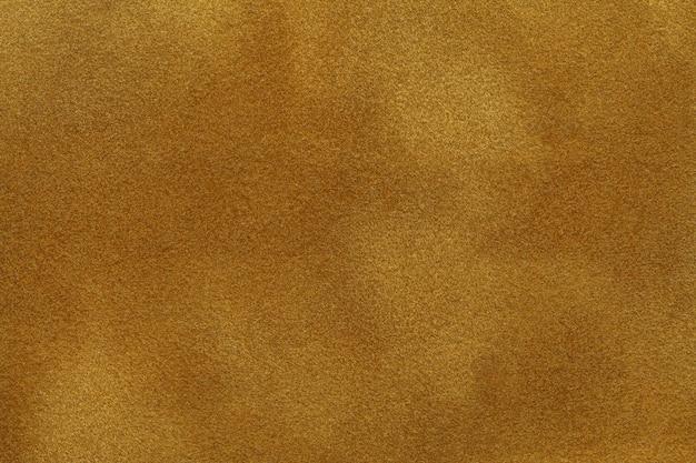 Hintergrund der dunklen goldenen veloursledergewebenahaufnahme. samtmatte textur aus gelbem nubukleder