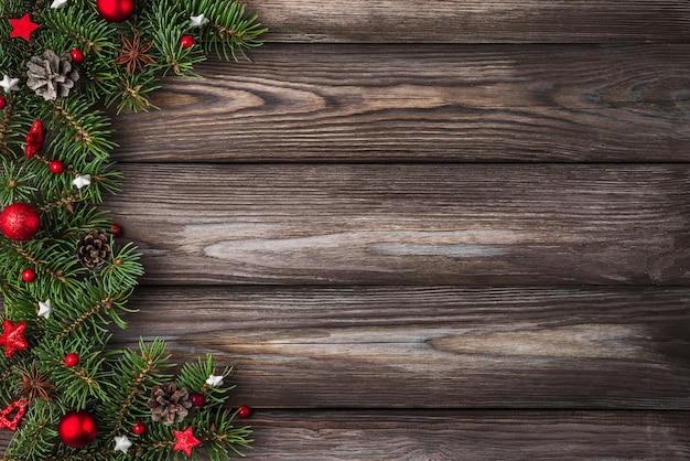 Hintergrund der frohen weihnachten und des guten rutsch ins neue jahr. tannenbaumzweige mit roten feiertagsdekorationen auf rustikalem holztisch. ansicht von oben. flach legen mit kopierraum