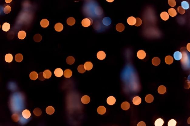 Hintergrund der gelben und blauen bokeh kugeln. goldener feiertag leuchtender hintergrund. defokussierter hintergrund mit blinkenden sternen.
