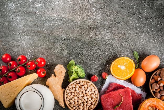 Hintergrund der gesunden diät. bio-lebensmittelzutaten, superfoods: rind- und schweinefleisch, hühnerfilet, lachsfisch, bohnen, nüsse, milch, eier, obst, gemüse. schwarze steintabelle, copyspace draufsicht