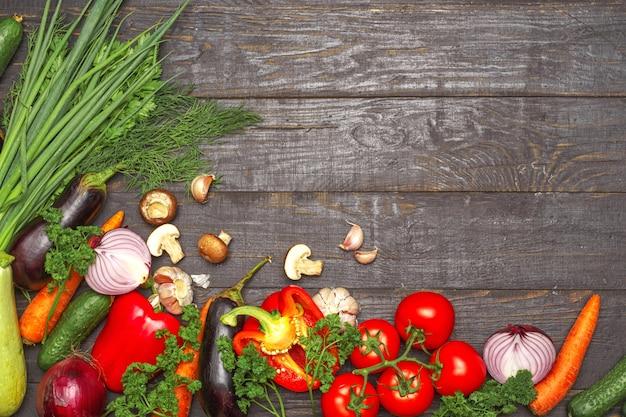 Hintergrund der gesunden ernährung. unterschiedliches gemüse der lebensmittelphotographie auf dunklem hölzernem hintergrund