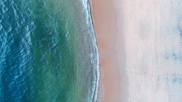 Hintergrund der luftdraufsicht, des strandes mit smaragdblauem wasser des schattens und des wellenschaums auf tropischem meer