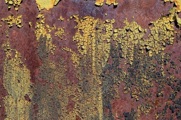 Hintergrund der rissigen mehrschichtigen farbe auf einer kleinen textur der rostigen metallwand