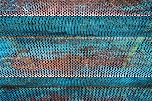 Hintergrund der rostigen blauen durchbohrten treppe