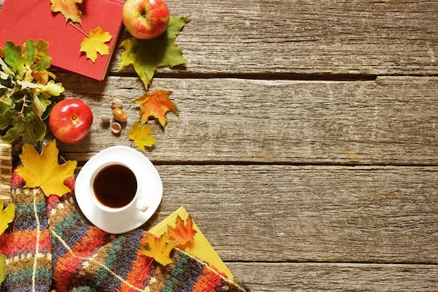 Hintergrund der roten, grünen und gelben blätter des herbstes, der äpfel mit tasse kaffee oder des tees mit büchern