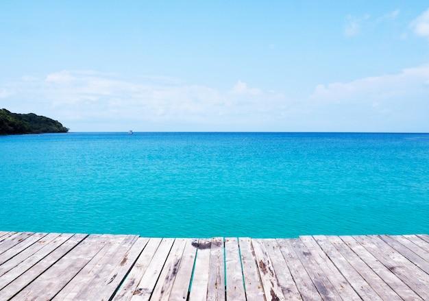 Hintergrund der schönen natur mit holzbrücke auf tropischem sommerstrand und blauem meer und himmel