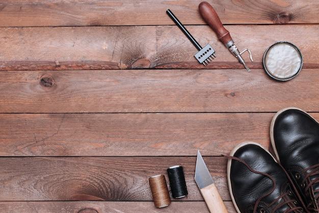 Hintergrund der schuhmacherwerkzeuge auf holztisch. set von lederhandwerkswerkzeugen.