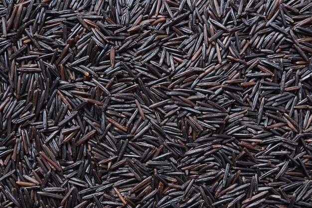 Hintergrund der schwarzen wilden veganen reisbeschaffenheit für etiketten und tapeten