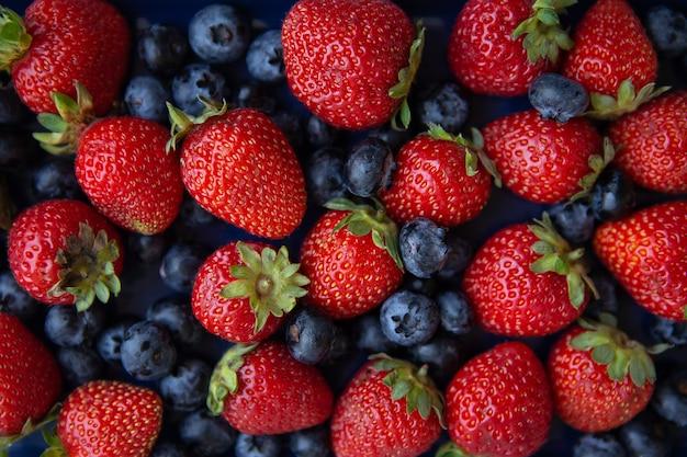 Hintergrund der sortierten frischen beeren der roten saftigen erdbeeren und der blauen blaubeerennahaufnahme