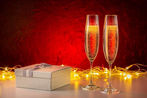 Hintergrund der weihnachts- und neujahrsfeiertage. geschenkbox mit champagner mit feuerwerk.