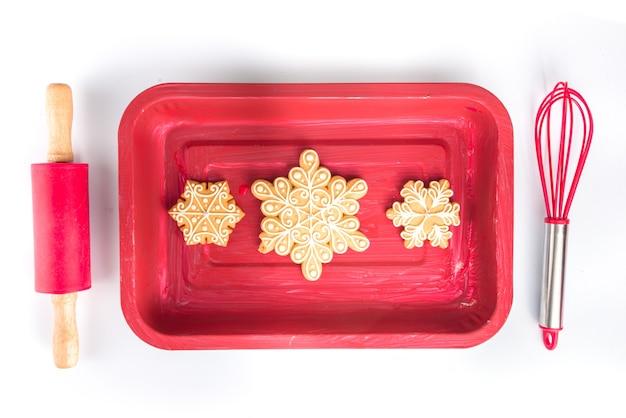 Hintergrund der weihnachtsbäckerei. vorbereitung auf die winterferien, weihnachtsverkauf einfach flach. rotes backblech, nudelholz, schneebesen mit traditionellem hausgemachtem lebkuchen, auf weißem hintergrund draufsicht