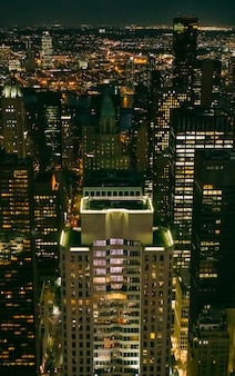 Hintergrund der wolkenkratzerfenster, die nachts in manhattan, new york city beleuchtet werden?