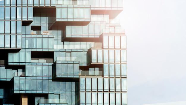 Hintergrund des blauen glases der modernen gebäudearchitekturwand, das im musterwürfel und im quadrat glasiert, überlappen mit beleuchtungssonnenlicht