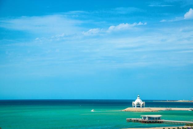 Hintergrund des blauen himmels mit schönen wolken und des azurblauen meeres mit jachthafen im rahmen