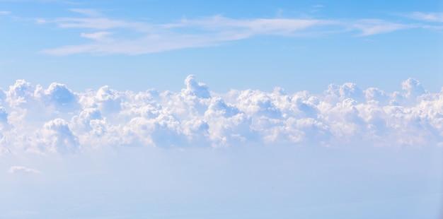 Hintergrund des blauen himmels und der wolken. blick aus dem flugzeugfenster