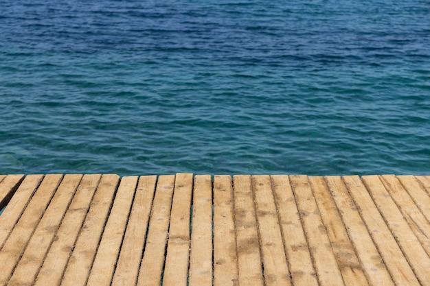 Hintergrund des blauen meeres und des hölzernen piers