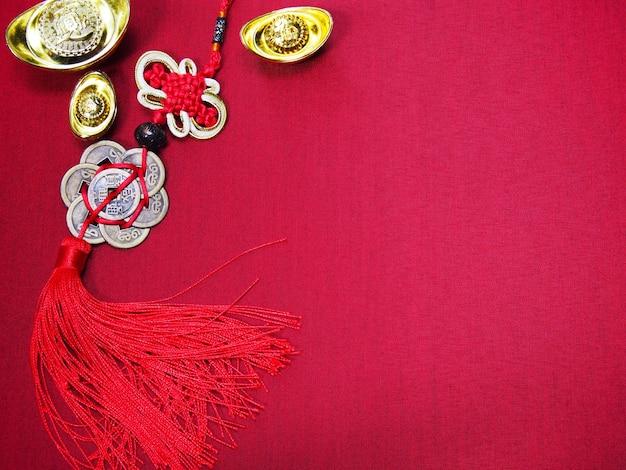 Hintergrund des chinesischen neujahrsfests. chinesisches glückssymbol und alte goldene barren auf rotem seidenstoff mit kopierraum.