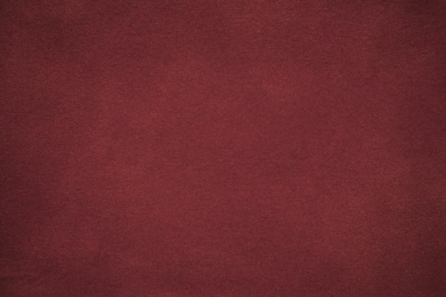Hintergrund des dunkelroten veloursledergewebes