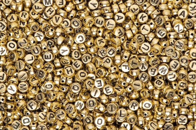 Hintergrund des englischen alphabets der metallischen goldperlen