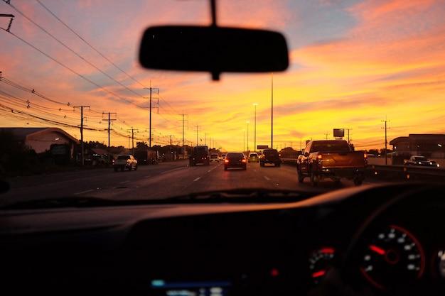 Hintergrund des fahrens eines autos auf der straße bei sonnenaufgang.