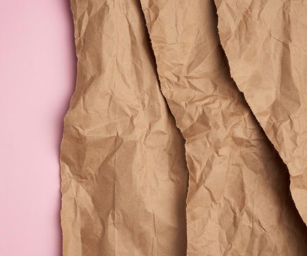 Hintergrund des geschichteten braunen zerrissenen papiers mit einem schatten auf einem rosa hintergrund