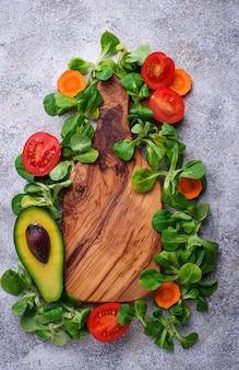 Hintergrund des grünen lebensmittels mit feldsalat, tomate und avocado