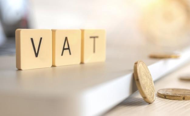 Hintergrund des mehrwertsteuerkonzepts. wort-mehrwertsteuer und münzen auf dem desktop. geschäfts- und managementfoto