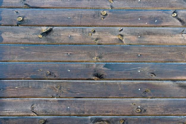 Hintergrund des natürlichen geknoteten braunen hölzernen zauns.