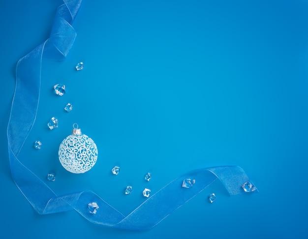 Hintergrund des neuen jahres. weiße weihnachtsbaumkugel auf blauem hintergrund mit exemplar