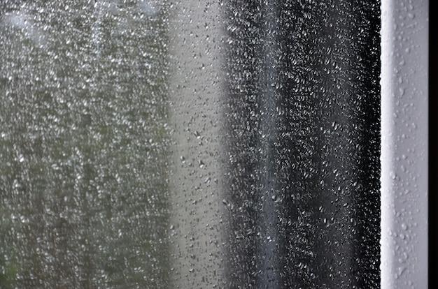 Hintergrund des regens fällt auf ein glasfenster. makrofoto mit flacher schärfentiefe