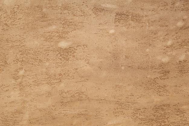 Hintergrund des strukturierten putzes der hellbraunen farbe. kunsthintergrund