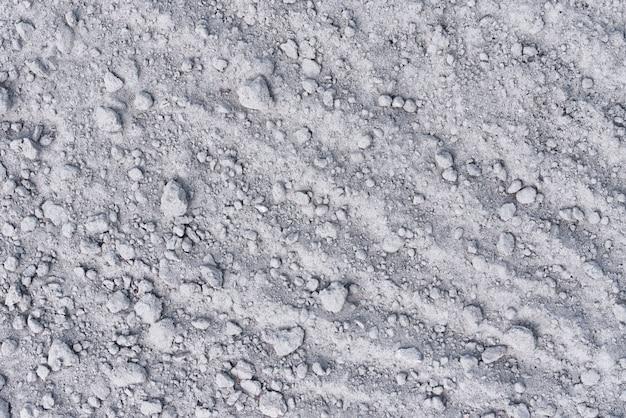 Hintergrund des trockenen bodens. sand mit steinen als textur