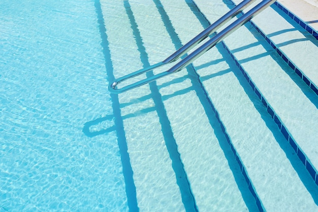 Hintergrund des wassers im blauen swimmingpool, wasseroberfläche mit einer sonnenreflexion