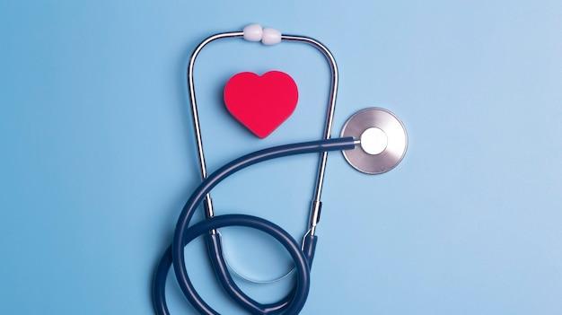 Hintergrund des weltherztages. herz als symbol für gesundheit, behandlung, wohltätigkeit, spende und kardiologie auf blauem grund mit einem medizinischen statoskop.