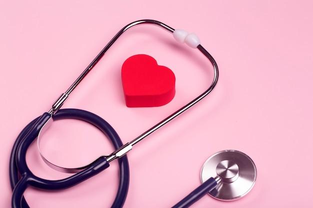 Hintergrund des weltherztages. herz als symbol für gesundheit, behandlung, wohltätigkeit, spende und kardiologie auf einem rosa hintergrund mit einem medizinischen statoskop.