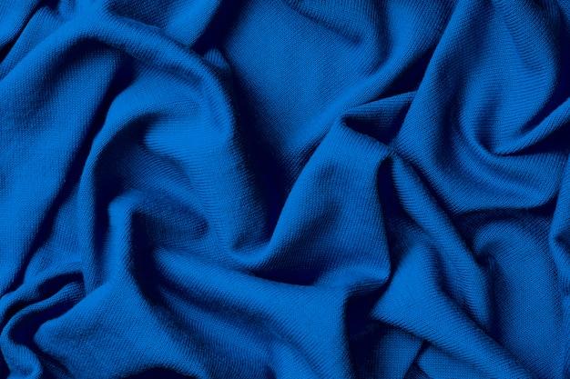 Hintergrund des zerknitterten blauen baumwollgewebes, tendenzfarbe des klassischen blaus des jahres 2020.