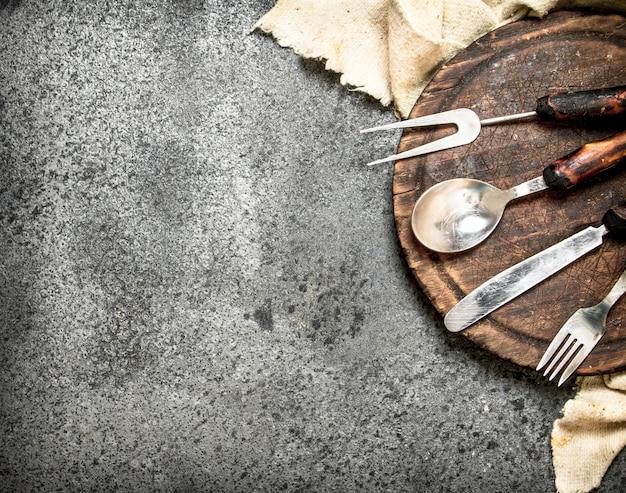 Hintergrund dienen. besteck auf dem alten brett. auf rustikalem hintergrund.