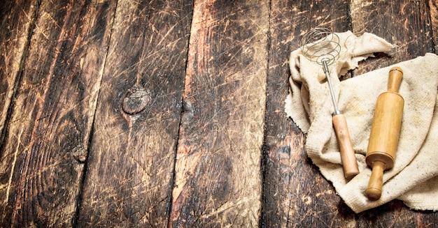 Hintergrund dienen. nudelholz und schneebesen auf einem alten stoff.