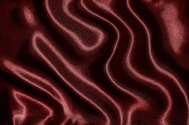 Hintergrund durch rotes gewebe, tapetenbeschaffenheit durch wellenartig bewegendes textilrot.