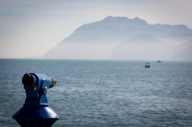 Hintergrund eines blauen panoramischen touristischen teleskops, welches das mittelmeer mit einem boot übersieht.