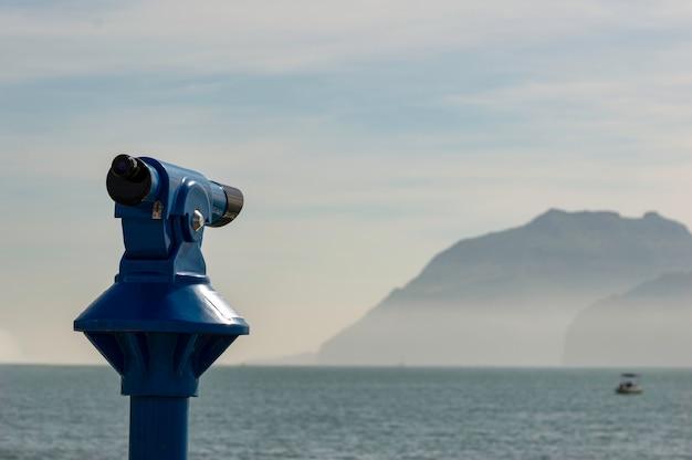 Hintergrund eines blauen panoramischen touristischen teleskops, welches das mittelmeer übersieht